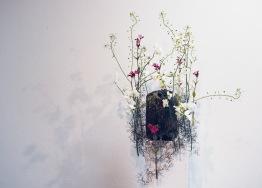 Die Aschenkapsel befindet sich in einer genähten Tasche aus Stoff. Um diese schwebt eine Wolke aus Draht, die die Leichtigkeit des Lebens symbolisiert. Die filigranen Blumen finden in dem Gerüst und den Reagenzröhrchen, die sich darin befinden, Platz. Sie strahlen eine leichte und edle Anmutung aus und geben der Wolke einen farblichen Akzent.