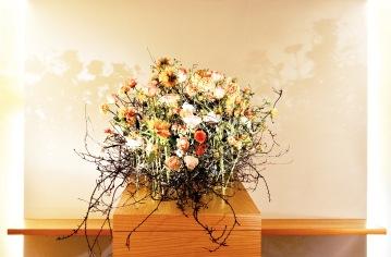 """Ein letztes Wort, eine letzte Erinnerung tragen die Hinterbliebenen, beim Gang zum Sarg, in ihren Gedanken. Jeder nimmt sich nacheinander eine Blume aus der Vase, die neben dem Sarg steht und gibt sie an einer gewünschten Stelle in das Schlehengerüst. Mit dieser Blüte nimmt der Trauernde Abschied und gibt seine letzten Gedanken dem Verstorbenen mit auf den Weg und sagt """"Auf Wiedersehen."""""""